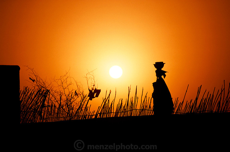 A woman carries some pots down to the Niger river to wash them at sunset in the W. African village of Kouakourou, Mali. Material World Project.