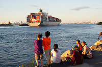 "Staten Islanders and visitors relax by the waterfront as the Cosco ""River Elegance"" container ship travels down the Kill van Kull in the New York and New Jersey harbor on Saturday, June 23, 2012.  COSCO is a state-owned Chinese shipping company, not the discount retailer in this case. (© Frances M. Roberts)"