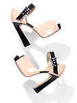 Pair of fashionable high heel platform womens shoes falling through the air isolated on white background
