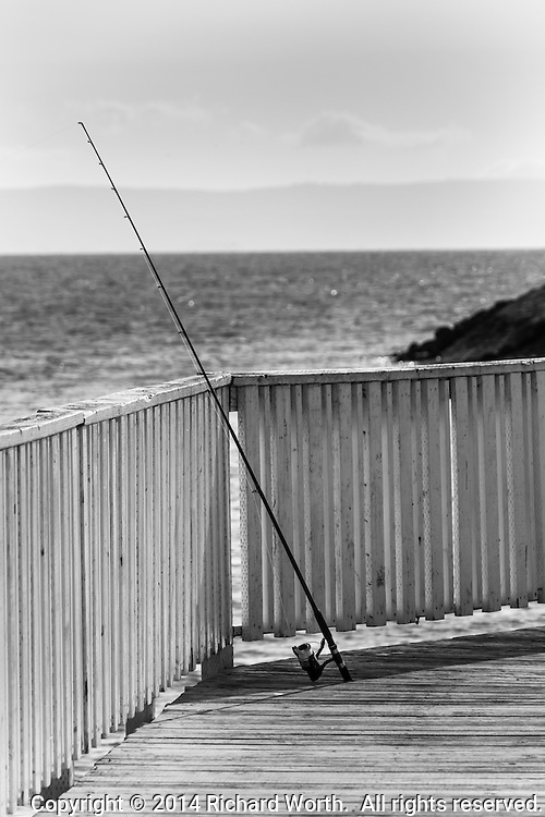 An unattended fishing pole stands, propped against the railing of the fishing pier at the San Leandro Marina.