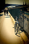 Couple walking along footpath in urban environment beside iron railings