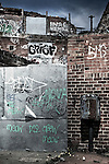 This image shows the back of a derelict building covered in graffiti in an urban area.