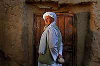 "Herat, Afghanistan - May 26, 2011...Hajji Saheb, the village elder of Ghorian District in the northwestern province of Herat poses for a portrait. In 1998, during the rule of the Taliban, he was responsible for contacting Mullah Omar (the Afghan Taliban spiritual leader) for the sentencing Shafiqa. The sentence was handed down over a satellite phone (by Mullah Omar) and was sentenced to death by stoning. When Hajji Saheb was asked by the photographer to pick up a rock the size of the ones thrown at the girl during the execution, he chose to this rock. Eyewitnesses reported that each rock thrown at Shafiqa weighed about six kilograms each (13 lbs.)...""One day earlier, around 10 o'clock, the husband handed her over to the government with her boyfriend. They received orders from Mullah Omar. They said in the radio that an adulterer and an adulteress have admitted that they escaped to Iran from Afghanistan, but the Iranian government repatriated them based on our request and they admitted that they fornicated more than 30 times. They brought the girl, Shafiqa. Her husband brought her near the ditch and told her to enter it. She asked where? He pushed her in the ditch. She fell head first. After that we started stoning. The stones hit the wall and fell down.  It was not her time to die. The ditch was full in 15 minutes. There was a mullah there who said it was her punishment in this world and the other world. She is clean now.""..*** NOTE TO EDITORS: All images conform to the standard industry practice of retouching, toning and color-correction for images. For a detailed description of the photoshop workflow used to tone each image, please refer to the ""Special Instructions"" section of the IPTC information. ***"