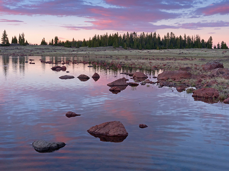 A colorful sunset reflects into a high alpine lake on the Aquarius Plateau in southern Utah, USA