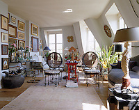 This attic living room of an apartment is a treasure trove filled with works of art and antiques yet still retains an air of cosy charm