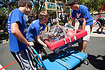 Toby Macaluso, Nicholas Bousse and Mike Hua, left to right, lift their robot back onto the cart after competing in the first round of RoboNanza June 27.