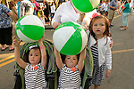 Garden City, New York, U.S. - June 6, 2014 -  Kelly of Garden City is with her 3 young daughters, who are holding green and white beach balls, at the Garden City Belmont Stakes Festival, celebrating the 146th running of Belmont Stakes at nearby Elmont the next day. There was street festival family fun with live bands, food, pony rides and more, and a main sponsor of this Long Island night event was The New York Racing Association Inc.
