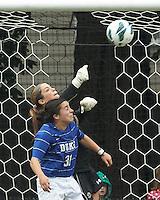 Boston College goalkeeper Alexandra Johnson (0) punches out a corner kick. Duke University defender Christina Gibbons (31).Boston College (white) defeated Duke University (blue/white), 4-1, at Newton Campus Field, on October 6, 2013.