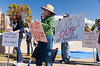 A crowd of people listen to a speaker while holding signs at the Occupy Orange County, Irvine camp on November 5.