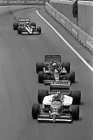 DETROIT, MI - JUNE 22: Nigel Mansell of Great Britain drives his Williams FW11/Honda RA166E ahead of Ayrton Senna of Brazil in the Lotus 98T/Renault EF15B and René Arnoux of France in the Ligier JS27/Renault EF4B during the Detroit Grand Prix FIA Formula One World Championship race on the Detroit Street Circuit in Detroit, Michigan, on June 22, 1986..