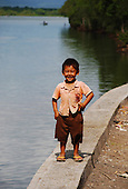 Small boy posing next to the river in western Bali, Indonesia.