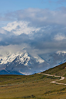 Mt McKinley, locally called Denali, is partially obscured by clouds, view of the Denali Park road leading to Eielson Visitor's Center, Denali National Park, interior, Alaska.
