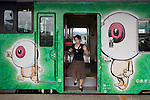A woman alights from a train decorated with characters by Shigeru Mizuki on a line servicing the home town of the manga artist in Sakaiminato, Tottori Prefecture, Japan..Photographer: Robert Gilhooly