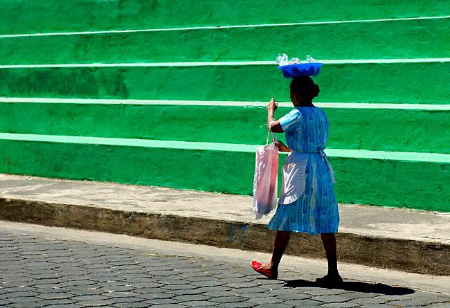 Street vendor balances her blue bowl of home made pastries on her head.