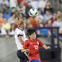 USWNT defender Becky Sauerbrunn  (4) and Korea Republic forward Yoo Younga (12) battle for head ball.  In an international friendly, the U.S. Women's National Team (USWNT) (white/blue) defeated Korea Republic (South Korea) (red/blue), 4-1, at Gillette Stadium on June 15, 2013.