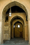 Cairo, Egypt -- A wooden door stands at the back of a series of arched arcades, on the Qibla side of the historic ibn Tulun mosque. © Rick Collier / RickCollier.com