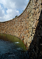 A carved wall built of local stone acts as a backdrop to a koi carp pond