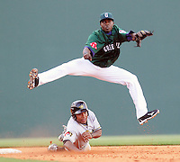 Greenville Drive shortstop Vladimir Frias 15)goes airborne to put out the West Virginia Power's Evan Chambers (53) at second and turn a game-ending double play on May 2, 2010, at Fluor Field at the West End in Greenville, S.C. Photo by: Tom Priddy/Four Seam Images
