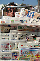 Man peaking through a rack of newspapers in Greece