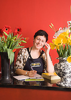A florist takes a customer order, photographed for a New Zealand Post editorial about small-business.