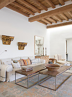 The positioning of a pair of gilt capitals on the living room wall reflects that of a pair of large antique wood and metal benches used as coffee tables