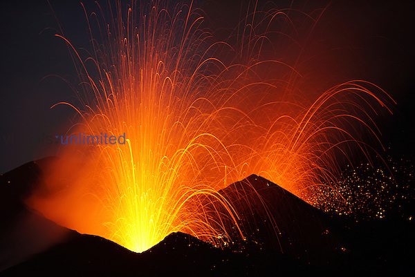 Nighttime Strombolian eruptions throw glowing volcanic bombs from craters along eruptive fissure. Fogo Volcano, 2014 eruption, Cape Verde