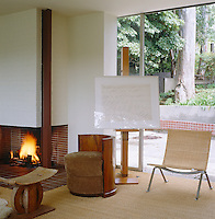 Next to the minimal-style brick fireplace in the living area an easel displays a framed work by Cy Twombly