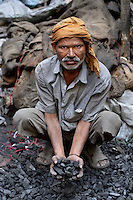 Man bagging coal in the backstreets of Amritsar, Punjab, India 2011.
