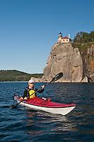 Sea kayaker on Lake Superior explores a rocky shoreline on Minnesota North Shore at Split Rock Lighthouse State Park.