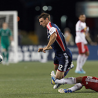 New England Revolution substitute midfielder Andy Dorman (12) tripped. In a Major League Soccer (MLS) match, the New England Revolution (blue) tied New York Red Bulls (white), 1-1, at Gillette Stadium on May 11, 2013.