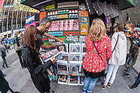 "Customers browse magazines at ""T. SQ Newsstand"" in Times Square in New York on Friday, October 9, 2015. Created by the artist Kimou ""Grotesk"" Meyer with Victory Journal and Juxtapoz Magazine, the pop-up displays and sells art and culture zines created by a litany of artists. It will be in business at the crossroads of the world until October 18. (© Richard B. Levine)"