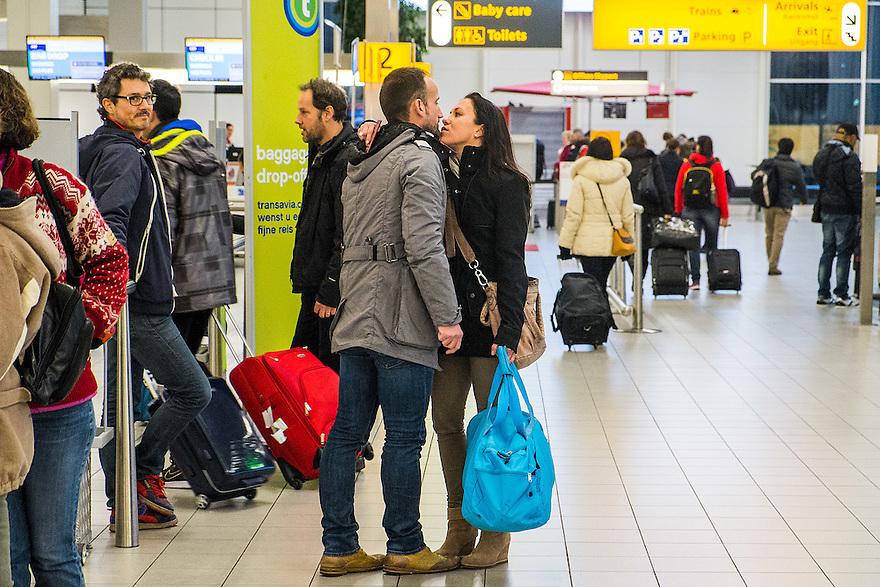 Nederland, Schiphol, 9 febr 2014<br /> Drukte op luchthaven Schiphol. Stel neemt afscheid van elkaar voor ze de gate in gaan.<br /> <br /> Foto: Michiel Wijnbergh