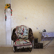 An Arabian belly-dancing scene on a rug sits on an armchair in a new house in the new part of the Sintesti Roma camp.  Arabian scenes are very popular within the camp, with wall murals depicting Arabian scenes also.