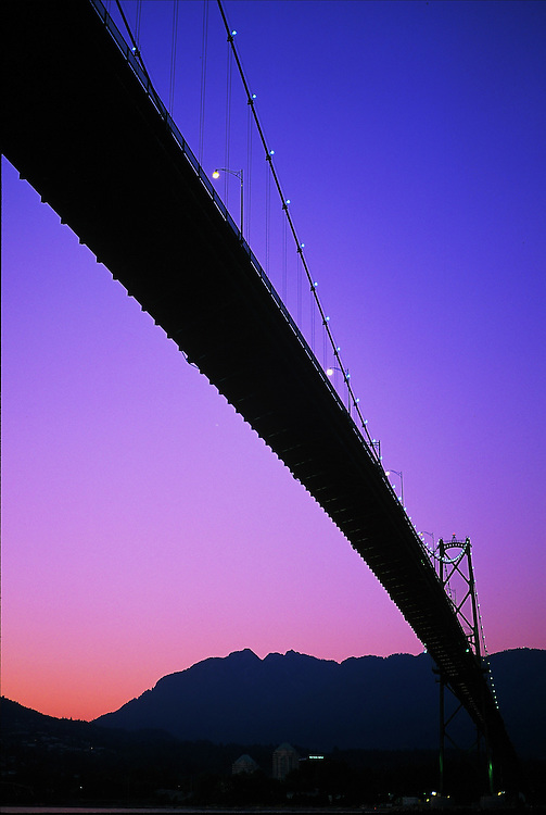 The Lions Gate Bridge stretching from Vancouver to North Vancouver, taken from the Stanley Park seawall at sunset in summer.