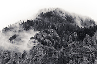 Tall mountain crags and columnar basalt outcroppings are seen with tall evergreen trees shrouded in foggy mist decending down the mountain in this black and white rendering landscape orientation