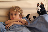 Little girl watching TV in bed, surrounded by her favourite stuffed animals.