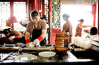 A member of kitchen staff washes dishes at The west Lake Restaurant. There are no dishwashing machines at the restuarant. Able to seat up to 5,000 people at one sitting, The West Lake Restaurant is the biggest Chinese restaurant in the world. Each week its diners, who staff are taught are 'the bringers of good fortune', devour 700 chickens, 200 snakes, 1,200 kgs of pork and 1,000 kgs of chillis. Its 300 chefs cook in five kitchens and its staff total more than 1,000.It is fully booked most nights.