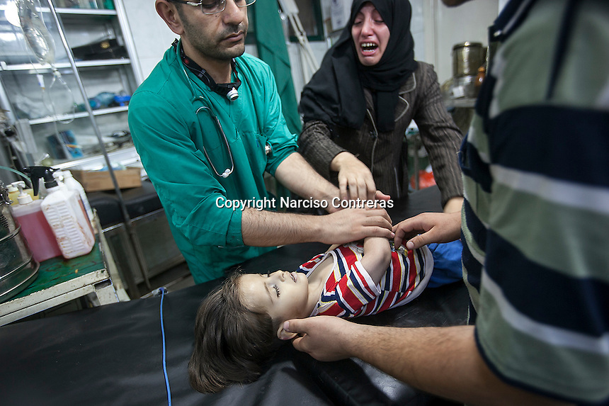A Syrian woman reacts as Dr. Osman (left) declares dead the woman's daughter, after the girl arrived injured by an aircraft attack to the Dar Al-Shifa hospital in the rebel-controlled area of Aleppo, Syria. September 04, 2012.