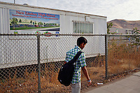 Lindsay, California, September 5, 2012 - Student walk past trailers set up for the construction of Lindsay High School, which was completed in 2010. The school of nearly 1,000 students is home to a mostly working class population, where agriculture plays an important role. ..Lindsay High School began building a competency-based education model about 7 years ago, fully implementing it just over three years ago and is set to graduate its first class this school year. This model does away with traditional grading and pass/fail for grades. Instead students are expected to achieve proficiency in a range of areas in each class, where a 3 (equal to a traditional B) is passing; A 4 is considered intensive and usually denotes college bound. Says Principal Jaime Robles, ?This allows students to learn at there own pace. If a student is advanced, they can move ahead, and if a student is lagging, they get the support they need.? Part of this model allows for students who are more advanced dig deeper and push harder and truly move ahead of others. Because they are ahead, some spend the extra time learning more, others take concurrent classes at the nearby community college and some choose to graduate early to start their path. ?Each student has their own set of goals,? says English teacher Amalia Lopez, ?Whatever their goals are, we support them.?.Slug: DD_ CompetencyByline: Daryl Peveto / LUCEO for Education Week