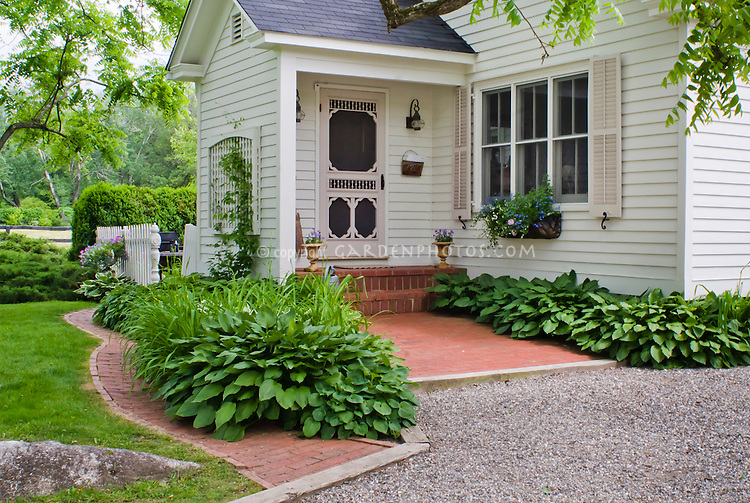 Curb appeal, shaded front entrance porch of house with hostas and ...