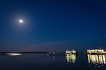 The last ferry from Whidby Island arrives under a full moon, at the Port Townsend ferry terminal.
