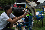 Native American , Chaske Hill Sicangu Lakota and Seneca , mother dressing and preparation of her 3 year old son for pow wow dance contest at the Thunderbird powwow in Queens, NY .