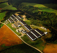 Scotland. Modern whisky distillery, Speyside. Aerial view of distillery, bond stores and surrounding countryside with fields of malting barley..