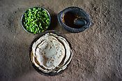 A detail of a regular meal for the entire family of Rekha RAMESH (Maize flour bread, green tomatoes and chilli paste) is placed for a photograph in Rekha's house in Dhawati VIllage of Khaknar block of Burhanpur district in Madhya Pradesh, India.  Photo: Sanjit Das/Panos for ACF