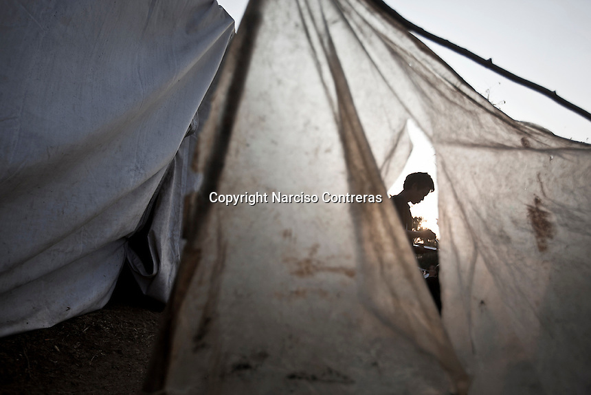 A Kachin refugee man eats a rice ration given by the WaPaNa NGO behind the tents at Seng Mai Pa IDP camp, one of the multiple camps settled outskirsts of Maiya Jang city. The camp gives shelter to two thousand displaced persons from the war-torn villages in Kachin State. The KIA positions around Maiya Jang city have been attacked by shelling and heavy artillery during months. Fierce clashes have taken place since the ceasefire was broken out by the Burmese army last June 2011. During months the fighting were spread out along the Kachin State leaving more than 40,000 displaced persons and refugees (a conservative estimating) in accord with the humanitarian aid groups.