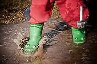 A toddler with green rubber froggy rainboots jumps and plays in spring mud puddles on a farm in northern Michigan.