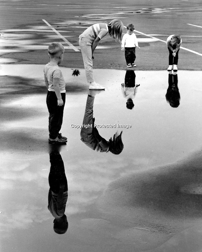 Kids check out their reflections in puddles of water at the Sun Valley Shopping center in Concord, Ca  parking lot after weekend showers. (1967 photo by Ron Riesterer)