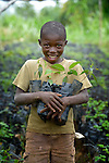 A boy holds seedlings in a plant nursery in Despagne, an isolated village in southern Haiti where the Lutheran World Federation has been working with residents to improve their quality of life. The LWF-sponsored nursery helps residents combat their country's rampant deforestation.