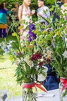 Fresh local flowers in mason jar bouquets on  wedding day.