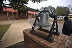 Mary Johnson walks past the bell outside of Oxford Elementary, in Oxford, Miss. on Tuesday, February 26, 2013. The bell will be returned to Burns Belfry Church.